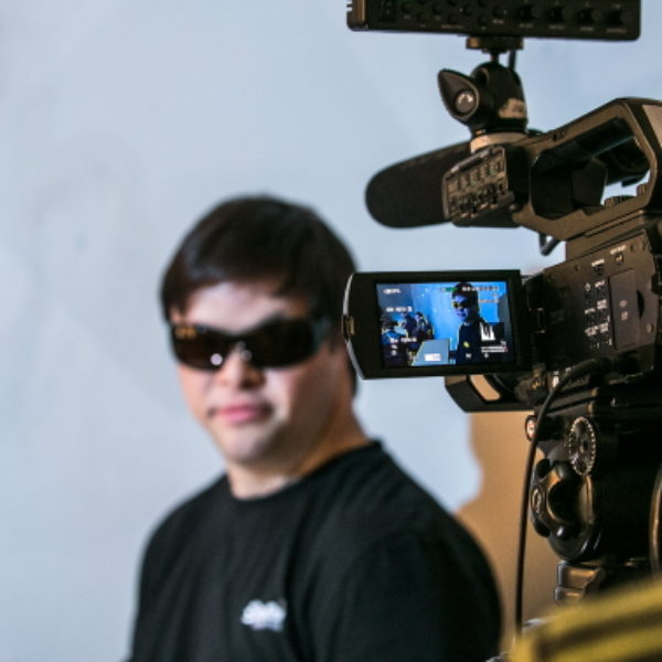 A man in black clothes and sunglasses is filmed by a camera