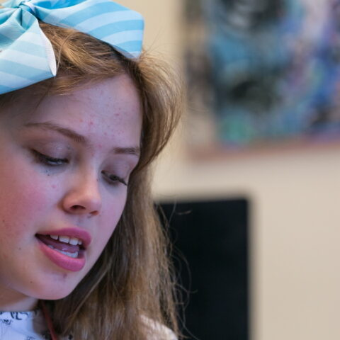A photo of a girl with a blue bow in her hair. Her eyes are cast downwards as she sings.