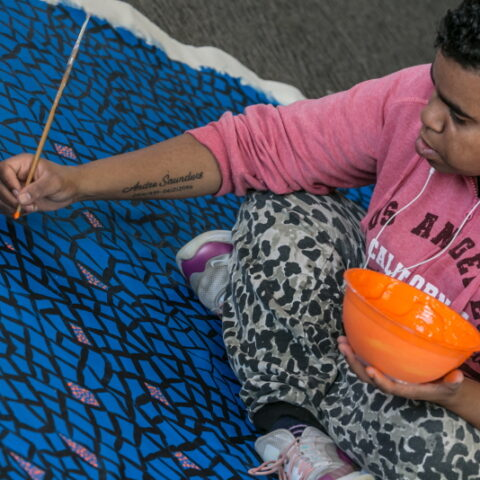 A young Aboriginal woman sits cross-legged painting a work on a large canvas and holding a bright orange bowl of paint