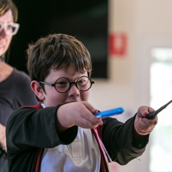 A boy dressed as Harry Potter points his wands as an adult staff member looks on