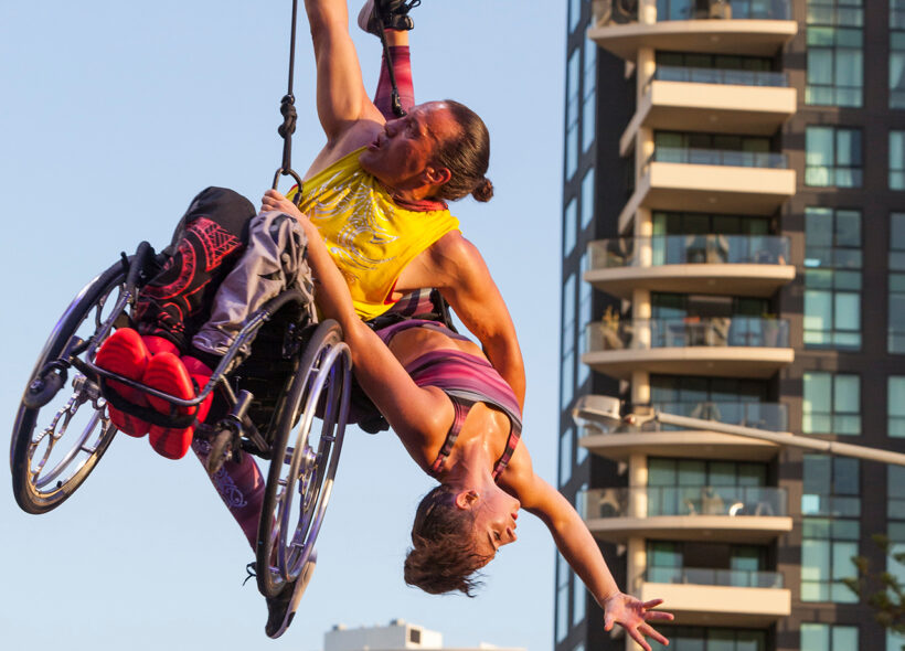 Maori artist Rodney Bell hangs in his wheelchair in mid-air, holding onto female performer Brydie Colquhoun with one arm