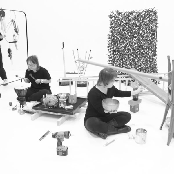 Three musicians are creating sound within an installation of various objects and hanging instruments.