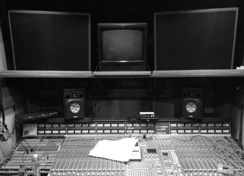 A black and white group image of a large audio mixing desk with speakers and screens.