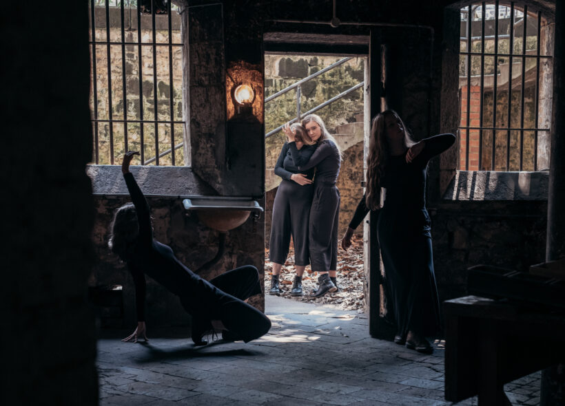There are four dancers dressed in black, pictured in the historic underground J Ward Asylum kitchen surrounded by bluestone floors and walls. The windows are barred, with an old gas light emitting a soft glow that pierces through the cold, dark interior. Two of the dancers in the foreground move in tableau through the darkness, and two dancers can be seen embracing through the open doorway in the light of day.