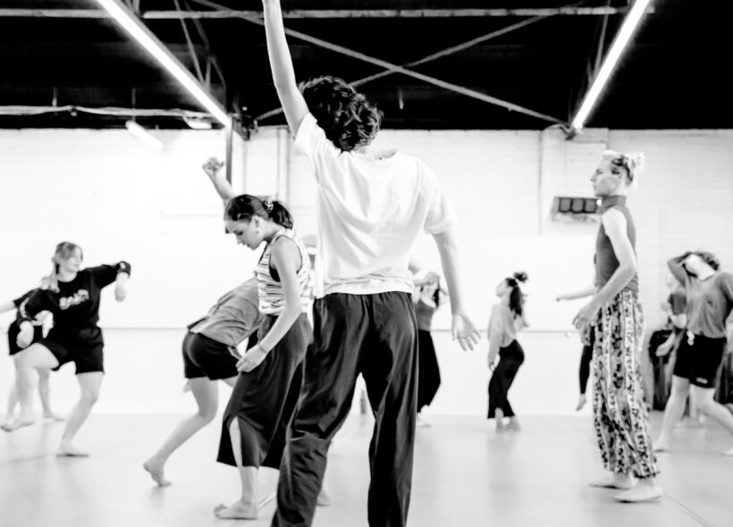 Black & white image of dancers moving variously in a white walled studio