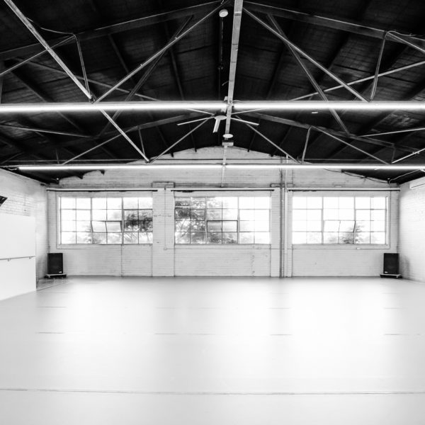 Image shows a dance studio in a warehouse space, with thin light beams hanging from a black, sloped ceiling, wide windows and white brick walls