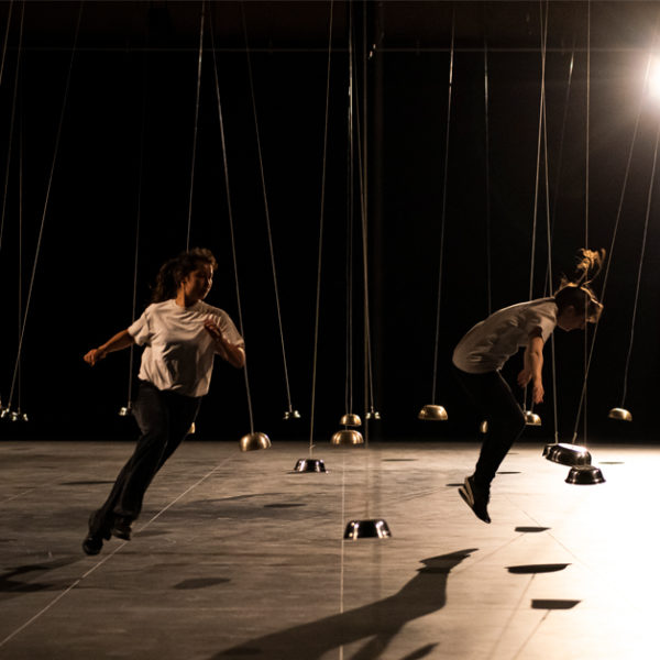 Dancers running dynamically under stage lights between small hanging domes