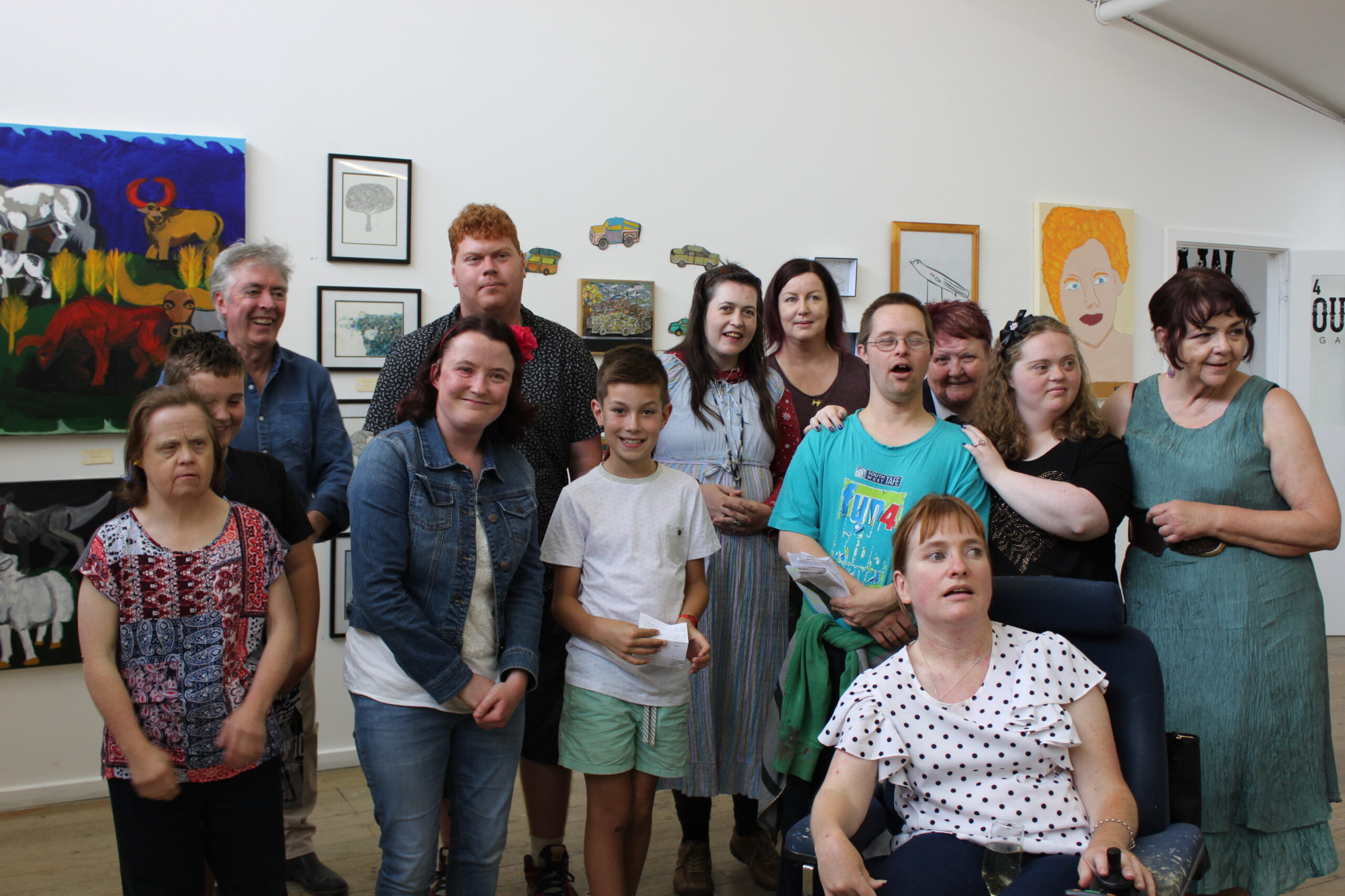 A group of nine artists and three mentors at the launch of the Mentors and Makers 2 exhibition for artists with disabilities and their mentors