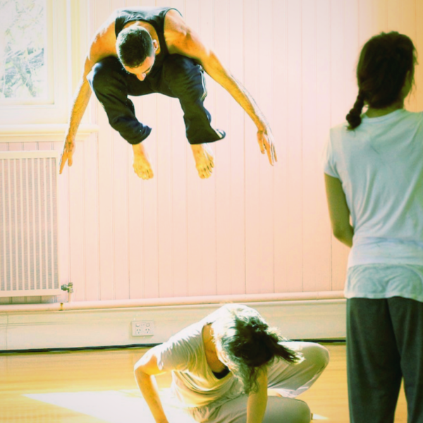A dancer leaps in the air in the background, another dancer crouches in the foreground and a third dancer stands to the side, their arm raised.