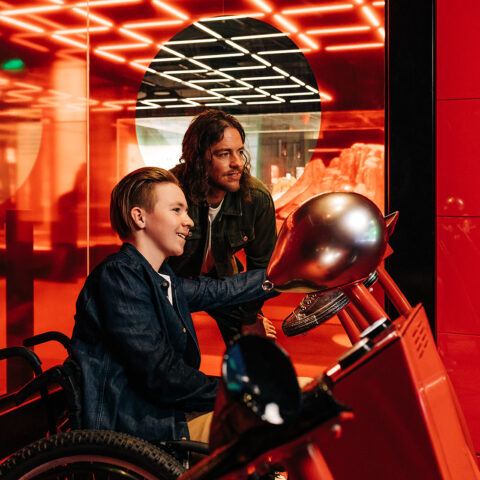 Boy in a wheelchair with man standing next to him. They are using the Foley machine at The Story of the Moving Image exhibition.