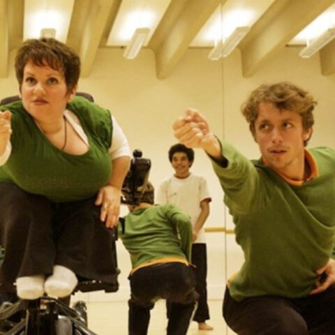 A woman in a wheelchair and a man crouching reach forward towards the camera. Behind them is a mirror in which a man in a white t-shirt is smiling