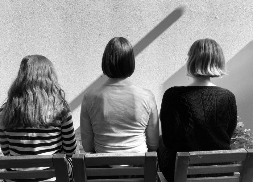 black and white image of the back of three people