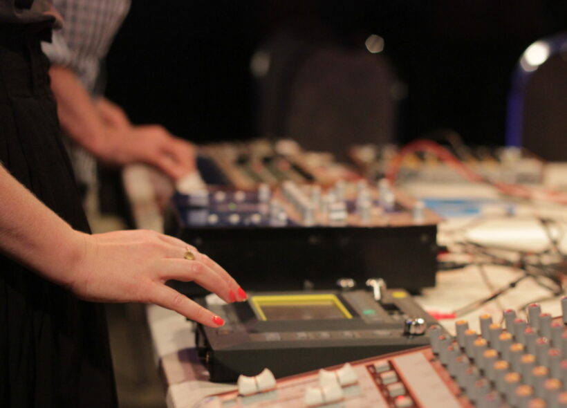 A woman's hands operating devices in a sound recording studio. In the centre are the words HACK SOUNDS in yellow font.