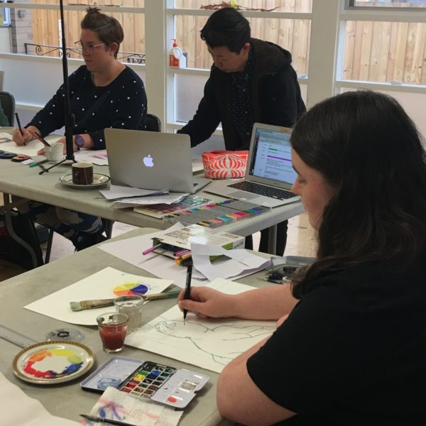 Image of life class in progress. A group of people sitting at tables learning watercolours.