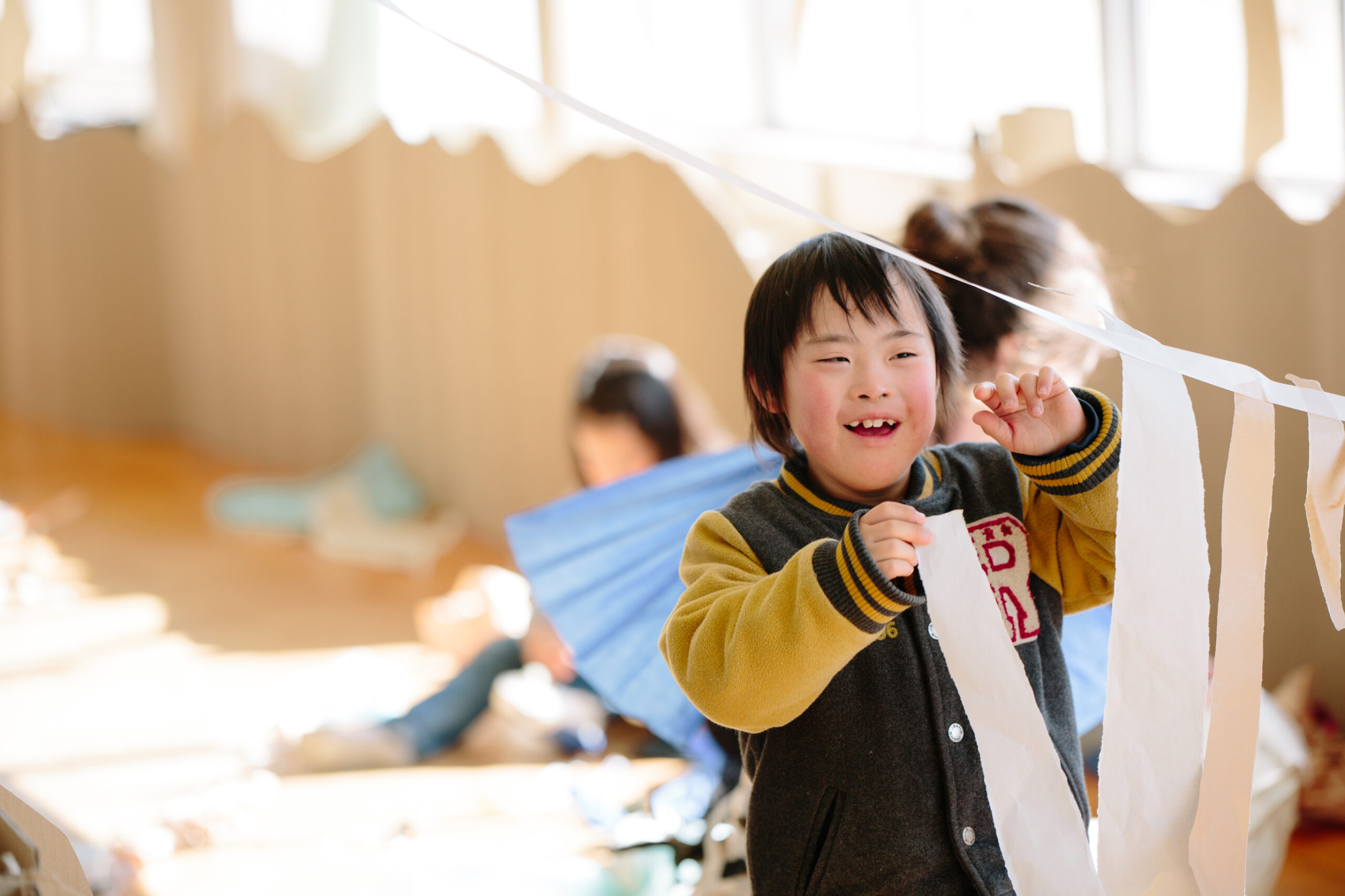 A Paper Planet production photo from Japan. A child with dark hair, wearing a black and yellow baseball jacket, joyfully hangs long strips of white paper on a suspended piece of tape. A sunlit room lined with brown cardboard and other children creating with paper are visible in the background.
