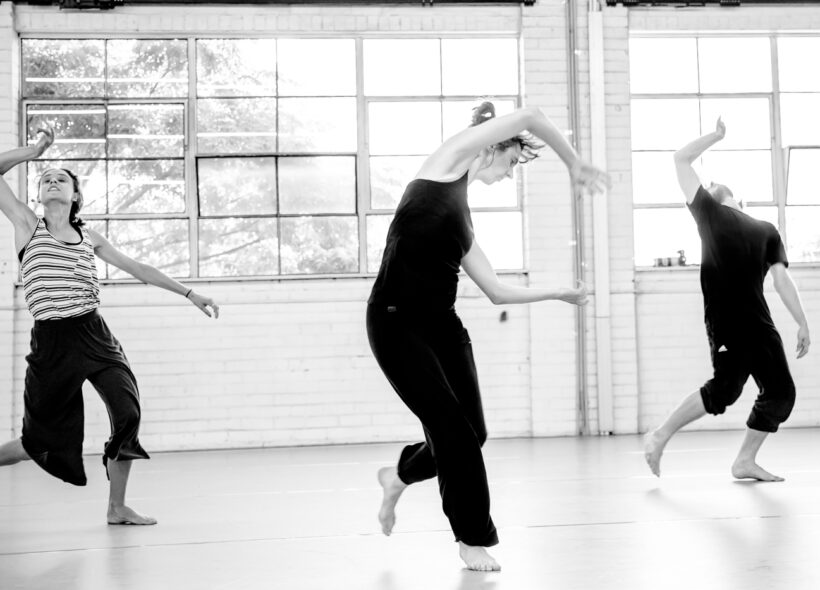 3 dancers move dynamically in front of a large window in a greyscale image.