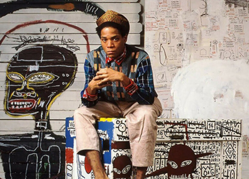 Photo of young Jean-Michel Basquiat sitting on a bench with his hands clasped together. The background and the bench are covered in his paintings.