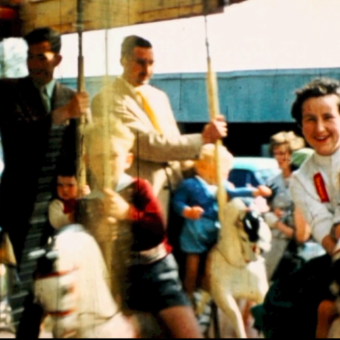 Still from 'Fond Inland', part of head_phone_film_poems. Kids, men and women riding on a carousel.
