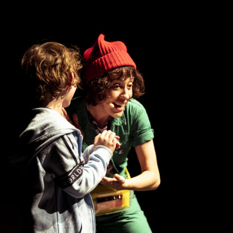 A photograph of a woman and a young boy standing in front of a black background. The woman wears a red hat, green dress and is smiling, wearing a microphone. The young boy is not facing the camera and is holding his hands together.