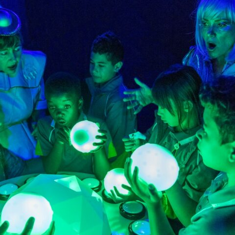 Four young children in school uniform surround a table along with three adults dressed in silver costume. One adult and two children are holding a lit orb. They are all lit in green and purple lighting.