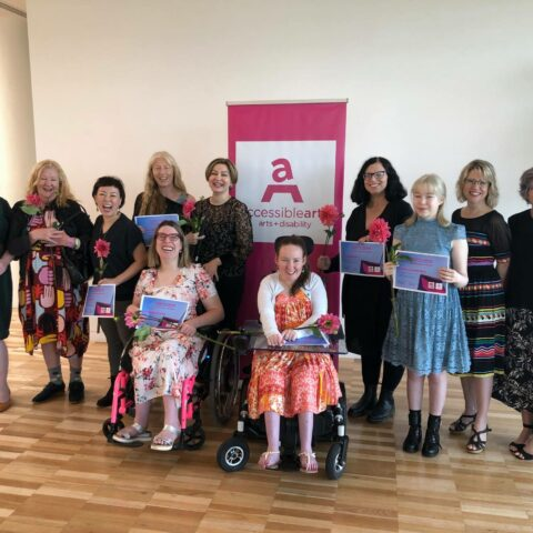 Eleven women in front of a pink Accessible Arts banner. They are smiling and holding pink flowers and certificates.