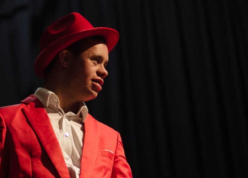 Strangeways Ensemble member Ethan Green in a red suit with a matching red fedora.